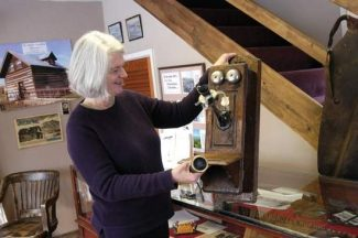 John Stroud | Post IndependentMt. Sopris Historical Society Museum caretaker Linda Criswell checks out an old-fashioned phone passed along from the Frontier Historical Society in Glenwood Springs last week. The museum is located in a homesteader's cabin that also belonged to the Thompson family.