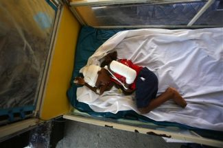 A boy injured during last week's earthquake lies on a bed at a hospital in Port-au-Prince, Monday, Jan. 18, 2010. Troops, doctors and aid workers flowed into Haiti on Monday even while hundreds of thousands of Tuesday's quake victims struggled to find water or food. (AP Photo/Ricardo Arduengo)