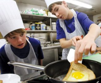 Dduring a breakfast cooking class at the Vail Cascade Resort in Vail, Stone Creek Charter School seventh grader Joey Travers, right, holds up the corner of his Toad in a Hole breakfast as sixth grader Jack Nichols checks to see how cooked it is before they flip it Wednesday