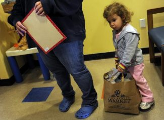 Cheyenne Hudspeth, 2, tries to pick up a bag of bread that she and her mom, Sydni Hudspeth, gathered up at the JeffCo Action Center, while they wait for their food allotment, Monday, April 12, 2010.   Poverty rates for children have significantly increased in Colorado suburbia, places like Jefferson County.  Judy DeHaas, The Denver Post