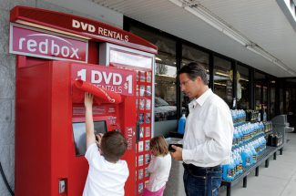 Kristin Anderson/Vail DailyAvon residents Dusty Boyd, right, and his children Denali, left, and Everest rent a DVD from a Redbox on Wednesday at Loaf 'N Jug in Eagle. Dusty said they reguarly use Redbox to rent movies.