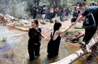 Kristin Anderson/Vail DailyEagle Valley Middle School seventh graders Cinthia Serrano, left, and Nora Lopez help classmates cross Eby Creek on Monday during an aquatic biodiversity study with the Gore Range Natural Science School in Eagle.
