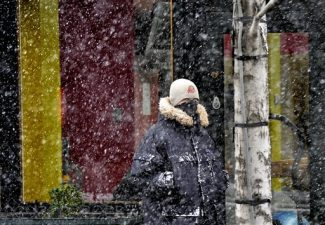 Bundled up for winter, a pedestrian makes his way though a snow shower on Howard Street near Main Avenue, Tuesday Jan. 17, 2012, in downtown Spokane, Wash.  Heavy snow is expected for the area on Wednesday. (AP Photo/Dan Pelle, Spokesman Review)