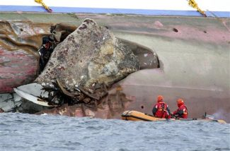 Firefighters on a dinghy look at a rock emerging from the side of the luxury cruise ship Costa Concordia, the day after it ran aground off the Tuscan island of Giglio, Italy, Sunday, Jan. 15, 2012.  The Italian Coast Guard says its divers have found two more bodies aboard the Costa Concordia. The discovery of the bodies brings to five the number of known dead after the luxury ship ran aground with some 4,200 people aboard on Friday night. (AP Photo/Andrea Sinibaldi, Lapresse)   ITALY OUT