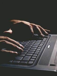 male hands on the keyboard,low key and high contrast,may suggest cyber cryme, hacking,spying