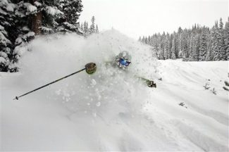 In this photo provided by Crested Butte Mountain Resort, Zach Kinler of Crested Butte, Colo. blasts through powder snow with his skis during the largest snow storms that is passing through the Colorado Rockies on Monday, Jan. 16, 2012. Crested Butte received more than a foot of snow. (AP Photo/Crested Butte Mountain Resort, Nathan Bilow)