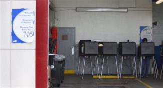 A lone voter cast her ballot in a west Miami fire station during the Republican primary election in Florida, Tuesday, Jan. 31, 2012. Mitt Romney entered the day as the heavy favorite over Newt Gingrich in Florida's winner-take-all primary. Rick Santorum and Ron Paul have ceded the vote to the two front-runners and planned to spend the day campaigning in Colorado and Nevada. (AP Photo/J Pat Carter)