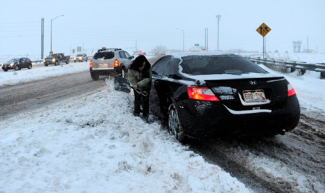 AP Photo/The Denver Post, RJ SangostiAngie Higdon tries to dig her car out, Friday, Feb. 3, 2012, on the on ramp from the Boulder Turnpike onto Highway 285 in Broomfield, Colo. A powerful winter storm swept across Colorado on Friday as it headed east, bringing blizzard warnings to eastern Colorado and western Kansas, and winter storm warnings for southeast Wyoming and western Nebraska.