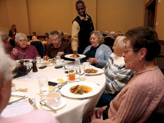 Server Soulemane, center, serves Laurraine Lamoureux, center right, her Thanksgiving pot roast lunch at the Seniors Thanksgiving luncheon at the Park Hyatt in Beaver Creek. The number of seniors living in Colorado's resort region is increasing as Baby Boomers reach retirement age