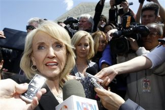 """Arizona Gov. Jan Brewer speaks to reporters outside the Supreme Court in Washington, Wednesday, April 25, 2012, after the court held a hearing on Arizona's """"show me your papers"""" immigration law. (AP Photo/Charles Dharapak)"""