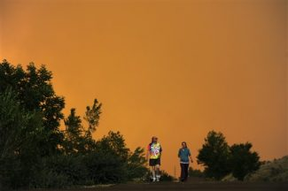 Diana and Donald Mangelsen walk near their home outside of LaPorte, Colo., as a wildfire burns in a mountainous area about 15 miles west of Fort Collins, Colo., on Sunday, June 10, 2012. Firefighters on Sunday were fighting wildfires that have spread quickly in parched forests in Colorado and New Mexico, forcing hundreds of people from their homes and the evacuation of wolves from a sanctuary. The Colorado fire grew to 22 square miles within about a day of being reported and has destroyed or damaged 18 structures. (AP Photo/The Denver Post, AAron Ontiveroz) MAGS OUT; TV OUT; INTERNET OUT; MANDATORY CREDIT