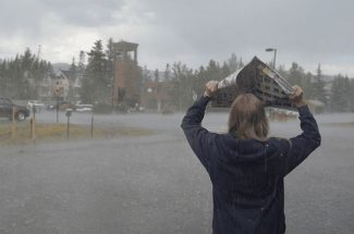 "Mark Fox/Summit DailyJackie Moberly covers herself from the rain in Frisco last week. Despite a few rain showers in Eagle County, and some heavy downpours in Summit County, fire danger remains ""extreme"" in Eagle County and ""very high"" in Summit County."