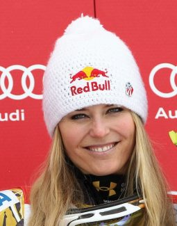 Lindsey Vonn, of the United States, celebrates on the podium her third place after completing a women's World Cup downhill on the Sochi Olympics course, in Krasnaya Polyana, near Sochi, Russia, Saturday, Feb.18,  2012.  Vonn clinched her fifth consecutive World Cup downhill title Saturday, although German rival and friend Maria Hoefl-Riesch won the race on the 2014 Sochi Olympics course. (AP Photo/Alessandro Trovati)