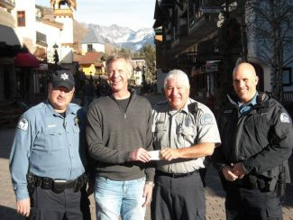 "Mark Hallenbeck, of Rocky Mountain Construction Group Inc., presents a check to the Vail Police Department for its ""Shop with a Cop"" program."