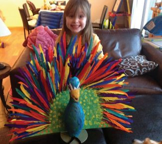 Kylie Kirkham, kindergartner at Red Sandstone Elementary School, proudly displays her homemade peacock created from one of the 300 bowling pins donated by Bol for the Pin It, To Win It school fundraiser Feb 1. Come support the school, kids and staff — tickets are still available for the event through the school!