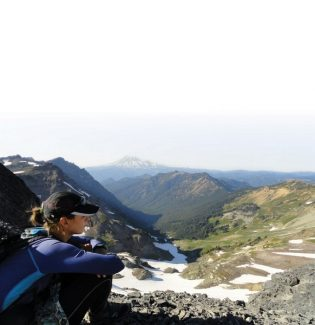 Elisabeth Perry pauses for a moment to enjoy the view along a Washington State section of the Pacific Crest Trail. Mount Rainier can be seen in the distance.