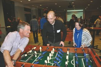 """Brad Ghent takes on The Cycle Effect's founder Brett Donelson and his daughter Christa Ghent in a game of Foosball at """"Foos and Brews"""" at the Westin Riverfront Resort and Spa."""
