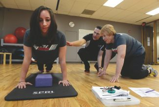 Student, Deena Christy, 61, right, from Letts, Iowa, works with National Personal Training Institute of Colorado instructor, Shawn Agnew, center, on analyzing fellow student, Ashli Bradley, left, during a push-up test April 4th, 2013 at the Institute in Lakewood Colorado April 4th, 2013.  Both Christy and Bradley are learning to become personal trainers, Christy wants to work with obese children and Bradley would like to work as a personal trainer for a cruise line. (Photo By Andy Cross/The Denver Post)