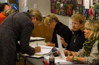 Connie Miller, left, fills out voter information while being helped by election judges Mary Caster, center, Carol McKown, middle right, and Holly Cole, right during election day Tuesday at the Vail Town Hall.