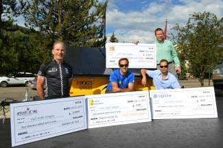 From left to right – Rob Levine of Antlers at Vail, Jason Weingast of Active Energies, James Deighan of Highline Sports and Entertainment and James Wilkin of First Bank present checks toward the purchase of Vail's Volts Wagon. The portable solar panel trailer will be available to event promoters for use at the town's events.