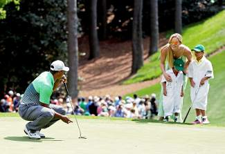 Lindsey Vonn and Tiger Woods' children Sam and Charlie watch as Tiger putts during the Par 3 contest at the Masters golf tournament Wednesday, April 8, 2015, in Augusta, Ga. (AP Photo/Charlie Riedel)