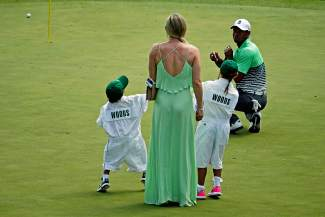 Lindsey Vonn and Tiger Woods' children Sam and Charlie try a catch a ball from Tiger during the Par 3 contest at the Masters golf tournament Wednesday, April 8, 2015, in Augusta, Ga. (AP Photo/Charlie Riedel)