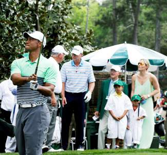 Lindsey Vonn and Tiger Woods' children Sam and Charlie watch as Woods' tees off during the Par 3 contest at the Masters golf tournament Wednesday, April 8, 2015, in Augusta, Ga. (AP Photo/Darron Cummings)