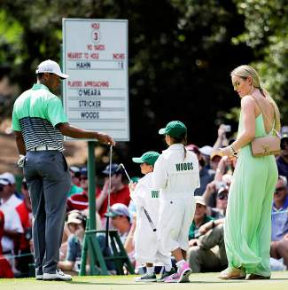 Lindsey Vonn walks with Tiger Woods and his children Sam and Charlie during the Par 3 contest at the Masters golf tournament Wednesday, April 8, 2015, in Augusta, Ga. (AP Photo/David J. Phillip)