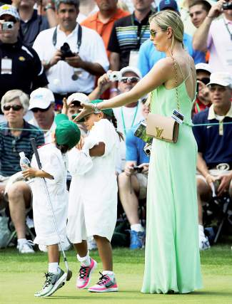 Lindsey Vonn tries to catch a ball fromTiger Woods with his children Sam and Charlie during the Par 3 contest at the Masters golf tournament Wednesday, April 8, 2015, in Augusta, Ga. (AP Photo/David J. Phillip)