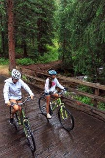 Sisters Seanna Faith and Emily Chaney, of Katy, Texas, cruise their bikes over a bridge while enjoying a rainy ride Monday on Vail Pass.