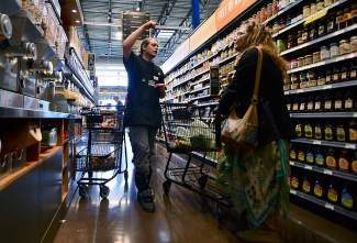 Eamon Cassidy, 24, of Silverthorne, helps a customer in the grocery section Tuesday, April 29, at the opening day of the Whole Foods Market in Frisco.
