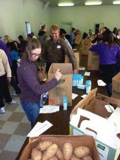 Volunteers assemble Salvation Army Thanksgiving food baskets for needy local families. This year the volunteers will gather at the site of the Winter Market and Holiday Fair at the Eagle River Center on Saturday.