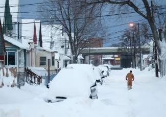 A man walks along a snow-covered street on Thursday, Nov. 20, 2014, in Buffalo, N.Y. A new blast of lake-effect snow pounded Buffalo for a third day piling more misery on a city already buried by an epic, deadly snowfall that could leave some areas with nearly 8 feet of snow on the ground when it's all done. (AP Photo/Mike Groll)