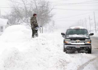 Jeremy Bauer stands on a snowbank next to a buried car outside his brother's house on Wednesday, Nov. 19, 2014, in Lancaster, N.Y. Lake-effect snow pummeled areas around Buffalo for a second straight day, leaving residents stuck in their homes as officials tried to clear massive snow mounds with another storm looming. (AP Photo/Mike Groll)