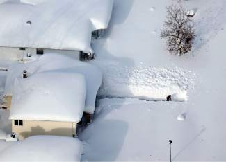 A man digs out his driveway in Depew, N.Y.,Wednesday, Nov. 19, 2014. The Buffalo area found itself buried under as much as 5½ feet of snow Wednesday, with another lake-effect storm expected to bring 2 to 3 more feet by late Thursday.  (AP Photo/The Buffalo News, Derek Gee)  TV OUT; MAGS OUT; MANDATORY CREDIT; BATAVIA DAILY NEWS OUT; DUNKIRK OBSERVER OUT; JAMESTOWN POST-JOURNAL OUT; LOCKPORT UNION-SUN JOURNAL OUT; NIAGARA GAZETTE OUT; OLEAN TIMES-HERALD OUT; SALAMANCA PRESS OUT; TONAWANDA NEWS OUT