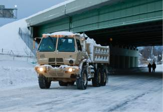A National Guard vehicle carries snow from a snow-bound neighborhood in south Buffalo  on Thursday, Nov. 20, 2014, in Buffalo, N.Y. A new blast of lake-effect snow pounded Buffalo for a third day piling more misery on a city already buried by an epic, deadly snowfall that could leave some areas with nearly 8 feet of snow on the ground when it's all done. (AP Photo/Mike Groll)