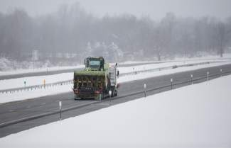 A truck carries a snow clearing vehicle along the New York State Thruway headed for the Buffalo area on Wednesday, Nov. 19, 2014, in Lancaster, N.Y. Lake-effect snow pummeled areas around Buffalo for a second straight day, leaving residents stuck in their homes as officials tried to clear massive snow mounds with another storm looming. A 132-mile stretch of the Thruway in western New York remains closed as as another round of snow is expected overnight and into Thursday. (AP Photo/Mike Groll)
