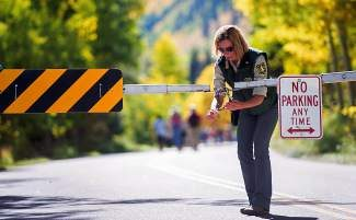 "U.S. Department of Agriculture employee Peggy Jo Trish, Maroon Bells manager, locks the gates on Maroon Creek Road on Tuesday as a result of the federal government shutdown. ""I was just told to leave,"" said Trish. ""It's a very sad day."""