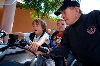 Bob Tutag, of the Vail Valley Motorcycle Foundation, shows a couple of Avon Elementary School students his motorcycle's radio on Thursday. Since 2003, the motorcycle group has been raising money to buy backpacks, school supplies and even breakfast for young students.