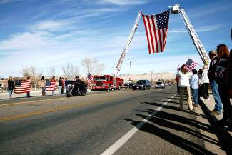 The  procession carrying the body of Air Force Capt. Will DuBois travels on Horizon Drive on Thursday under two Grand Junction fire trucks suspending an American flag. The procession traveled from the Grand Junction Regional Airport to Grand Valley Funeral Home.