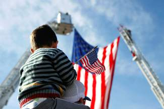 Henry Frappier sits on the shoulders of Frank Frappier as they wait Thursday for the  procession carrying the body of Air Force Capt.  Will DuBois to pass by on Horizon Drive in Grand Junction.