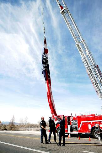From left, Matt Bollry, Matt Harmon and Tyler Nathe of the Grand Junction Fire Department prepare the American flag to be lifted into the air over Horizon Drive in Grand Junction, where the body of Air Force Capt. Will DuBois passed on Thursday.