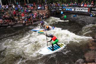 Athletes of the SUP Cross Finals try to stay on their boards at International Bridge, Sunday, in Vail. The race on Gore Creek is described as skier or boarder cross on standup paddle boards.
