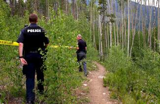 Sherff's deputies rope off a trail behind the crash scene at St. Anthony Summit Medical Center on Friday.