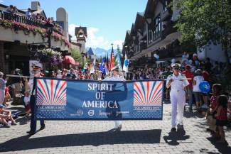 Veterans carry a banner dawning the Vail America Days theme for the Fourth of July parade down Gore Creek drive on monday.