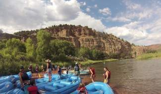 Riverfest partygoers prepare to float a stretch of the Colorado River Saturday between Red Dirt Road and Colorado River Ranch in Eagle County north of Dotsero.