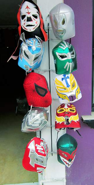 Mexican wrestling masks hang from the door of a vendor stall on a sidestreet winding through Sayulita.