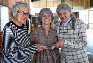 Ruth Walker, center, receives funds for Hospice of the Valley from rummage