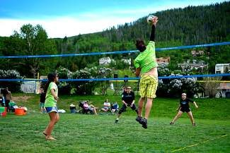 Lance Phair reaches to hit a set from his daughter Ashlyn, left, 9, and send the ball to the opposing team of Chris Powers and his daughter Myrrh, 11, during the King of the Mountain volleyball tournament in Eagle-Vail on Sunday. The family matchup was part of the final four, single elimination bracket style tournament for 12-and- under father and daughter teams.