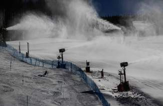 Snow guns blast icy particles onto a ski run while ski racers practice turns last November at Golden Peak in Vail.
